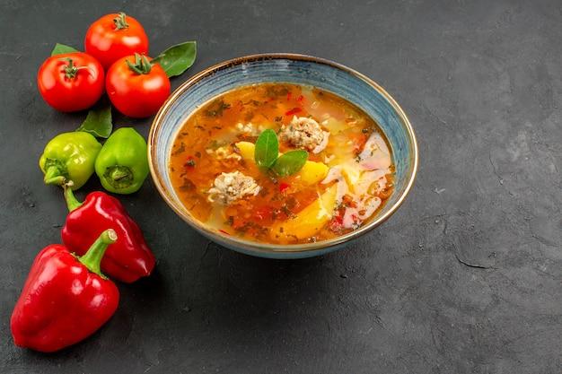 ダークテーブルソースの皿の色に野菜を添えたハーフトップビューのおいしいミートボールスープ