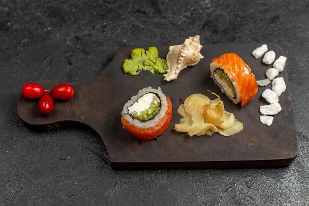Vista dall'alto di involtini di pesce a fette di pasto gustoso sushi con wassabi verde sul muro grigio