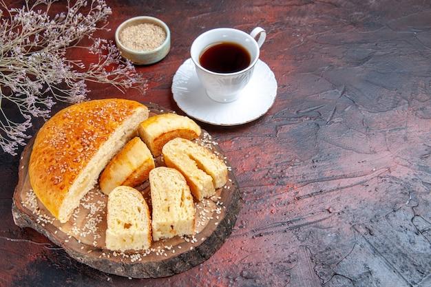 Вкусная сладкая выпечка, нарезанная кусочками с чаем на темном фоне, вид сверху