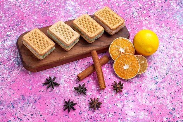 ライトピンクの背景にフルーツクリームを詰めたハーフトップビューのワッフルクッキー。 無料写真