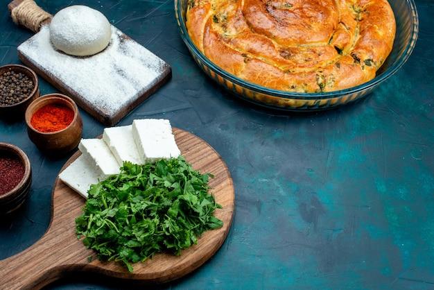 青の背景に緑のペストリーと調味料とハーフトップビューの白いチーズ。