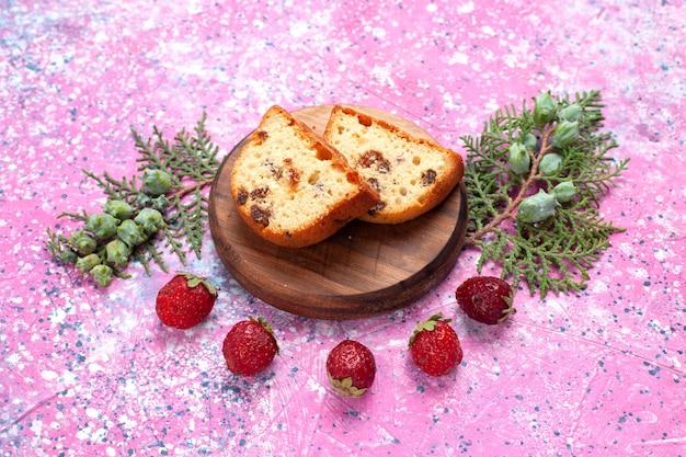 Вкусный сладкий и вкусный торт, нарезанный свежей красной клубникой, на розовом столе.