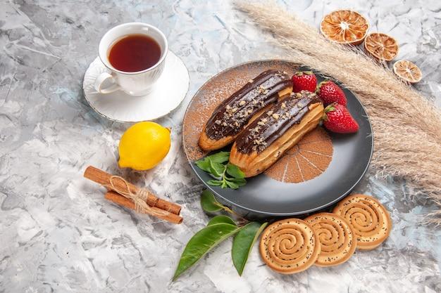 Eclair al cioccolato con vista a metà dall'alto con una tazza di tè su un biscotto da dessert con torta da tavola bianca