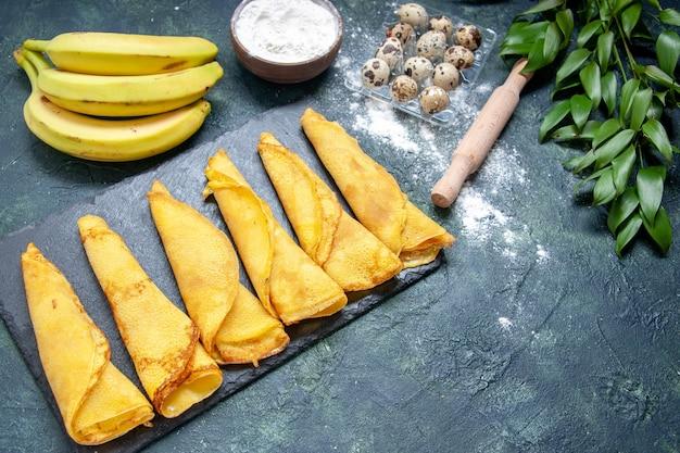 Deliziosi pancake con vista a metà dall'alto con banane su superficie scura