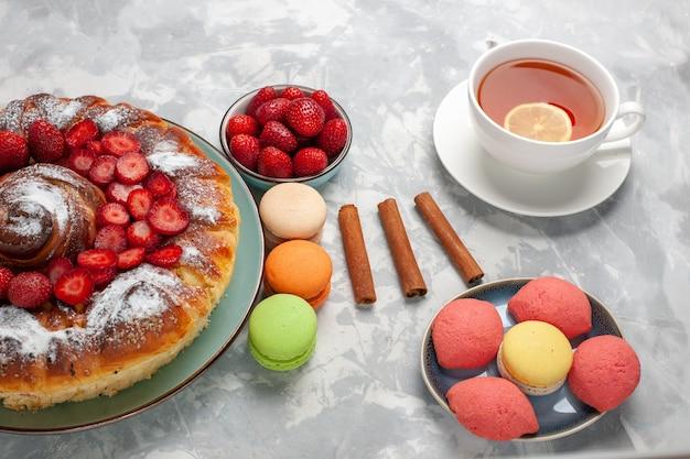 Torta di fragole gustosa con zucchero a velo e macarons e tè sulla superficie bianca