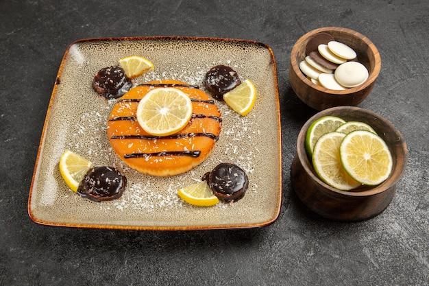ハーフトップビューおいしい甘いパイとチョコレートソースと灰色の背景にレモンスライスケーキパイビスケット生地甘いクッキー