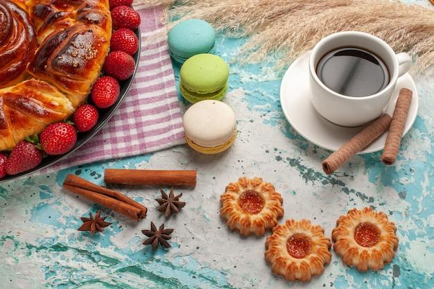 Torta dolce gustosa vista semi-superiore con macarons di fragole rosse e tazza di tè sulla superficie blu