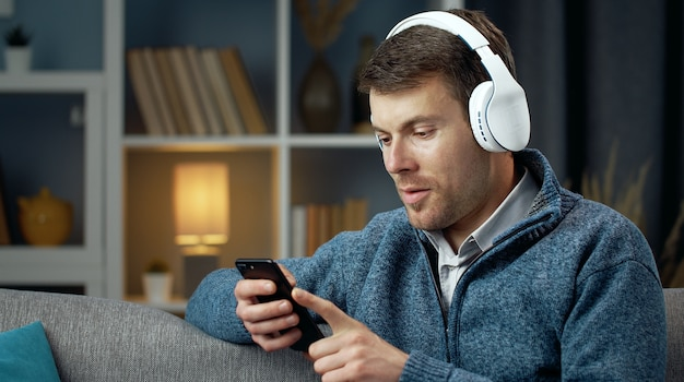 ソファに座ってスマートフォンとワイヤレスヘッドフォンを使用してカジュアルな嬉しい男の半回転の肖像画