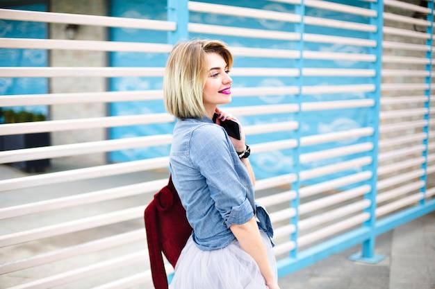 彼女の左を見ているスマートフォンを保持している明るいピンクの唇を持つ半回転の美しい女性