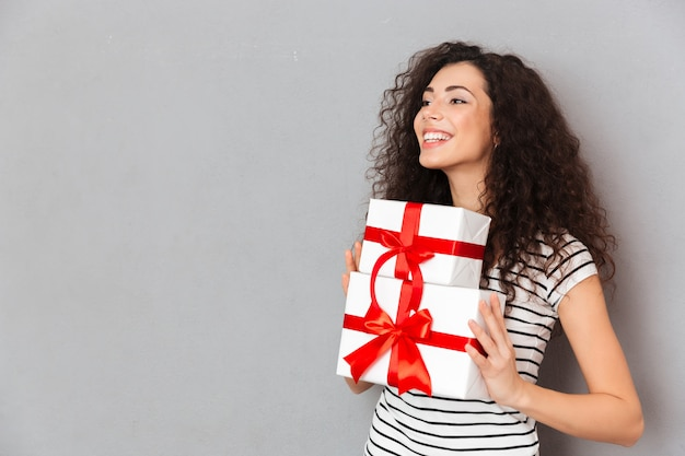 Half turned photo of gorgeous female in striped t shirt holding two gift wrapped boxes with red bows being excited and joyous over grey wall
