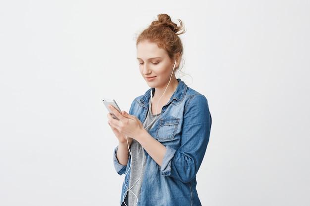 Ritratto a mezzo giro di giovane ragazza sveglia dello zenzero con capelli pettinati in panino, mandando un sms o navigando tramite smartphone mentre stando contro lo spazio grigio