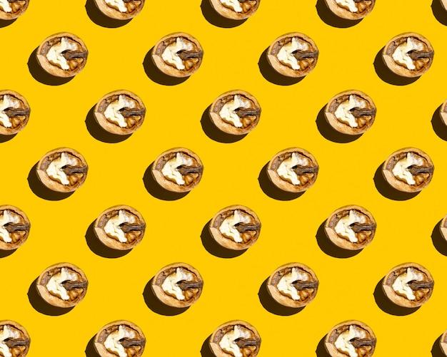 黄色の背景パターンに半分のクルミ