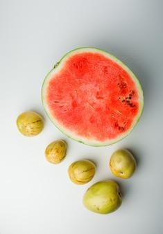 白のグラデーションの背景に熟したリンゴと半分のスイカ