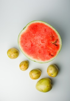 Half watermelon with ripe apples on white gradient background