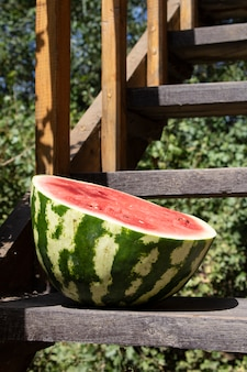 Half watermelon on wooden stairs, close up