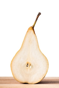 Half of williams or bartlett pear, slice, on wooden table with isolated white background.