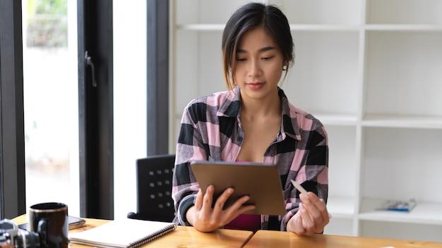 図書館に座っている間デジタルタブレットを使用してスコットジャケットの女性の半分の長さの肖像画
