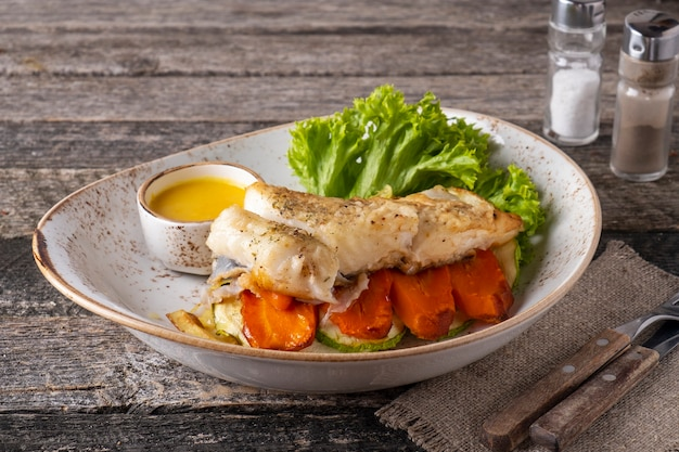 Halibut steak with baked vegetables on a plate