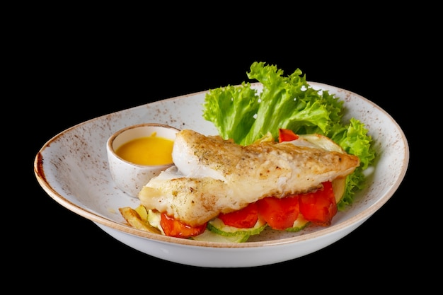 Halibut steak with vegetables isolated on black