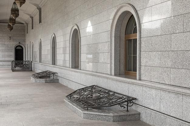 창문이있는 회색 빛나는 화강암 타일로 설계된 홀