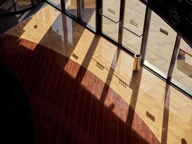 日没の太陽の影の床のガラスの入り口ショーケーストップビューでショッピングセンターのホール