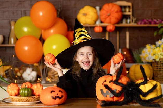 ハロウィーン、カボチャと暗いキッチンの大きなクモと魔女の衣装を着た子供の女の子は、ハロウィーンの休日を祝い、笑顔、喜び、そして浮気します
