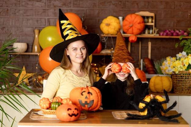 ハロウィーン、カボチャと暗いキッチンで大きなクモと魔女の衣装を着た子供の母と娘は、ハロウィーンの休日を祝い、笑顔、喜び、そして浮気します