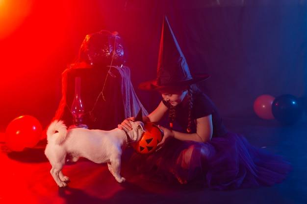 と遊ぶハロウィーンのカボチャと魔女の衣装でハロウィーンとお祝いのコンセプトの子供の女の子