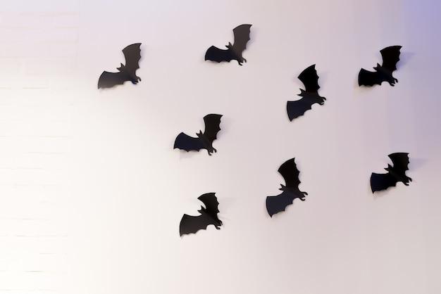 白い背景の上を飛んでハロウィーンと装飾コンセプトの黒い紙コウモリ