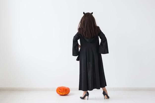ハロウィーンと休日のコンセプト-コピースペースのある明るい壁にジャック・オー・ランタンのカボチャを持った魔女の女性