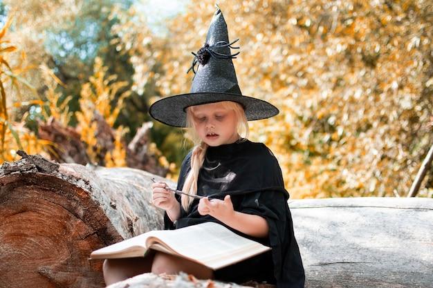 ハロウィーンと魔女。魔女の衣装を着た子供。子供は本と魔法の杖を持って木の上に座っています。秋、森