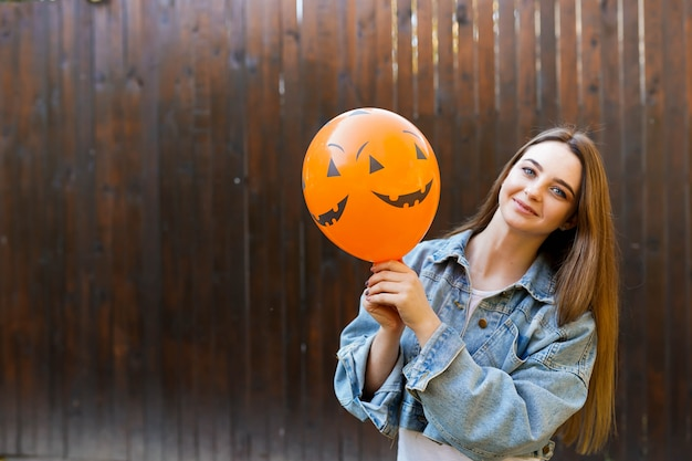 Halloween autumn background with girl holding orange air ballon