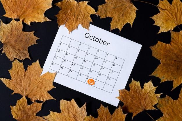 ハロウィーンの背景。 10月31日のマークが付いたカレンダーページと暗いテーブルトップビューに該当
