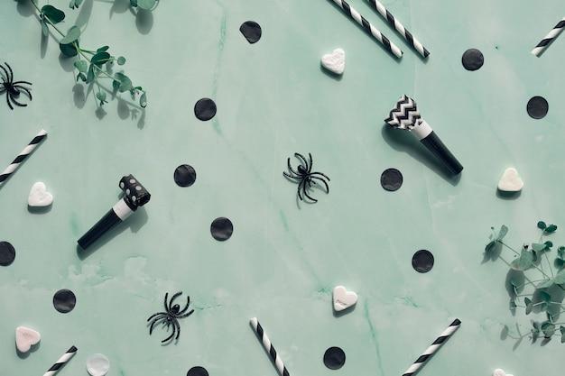 ミントグリーンの石のハロウィン背景。紙吹雪、砂糖のハート、パーティーの鳴り物、飲み物のストロー、黒いクモ。