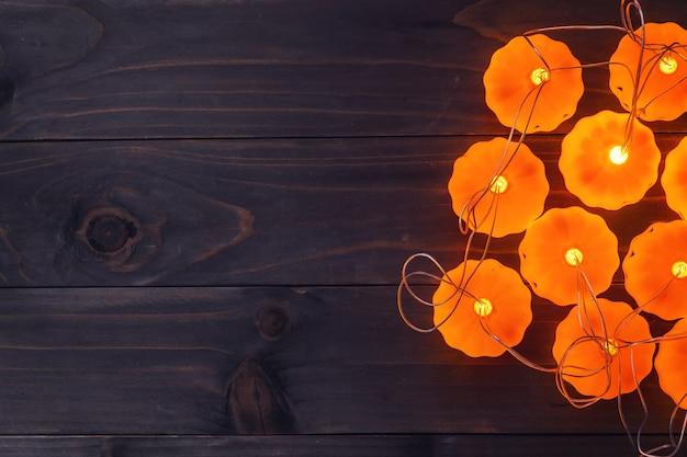 ハロウィーンの背景、木製のテーブルにカボチャのストリングライト