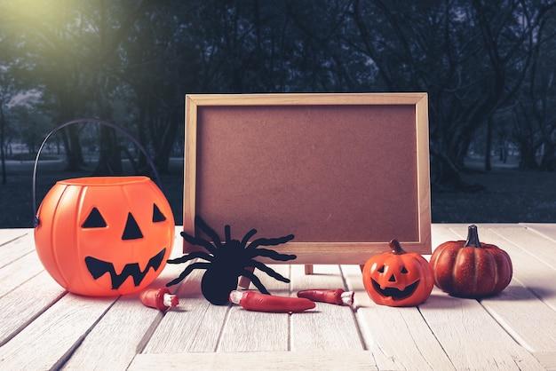 Halloween background. spooky pumpkin, chalkboard on wooden floor and dark forest. hallowee