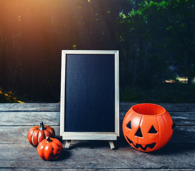 Halloween background. spooky pumpkin, chalkboard on wooden floor and dark forest
