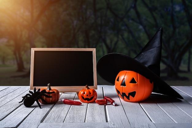 Halloween background. spooky pumpkin, chalkboard on wooden floor and dark forest.