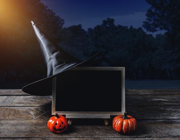 Halloween background. spooky pumpkin, witch hat, chalkboard on wooden floor
