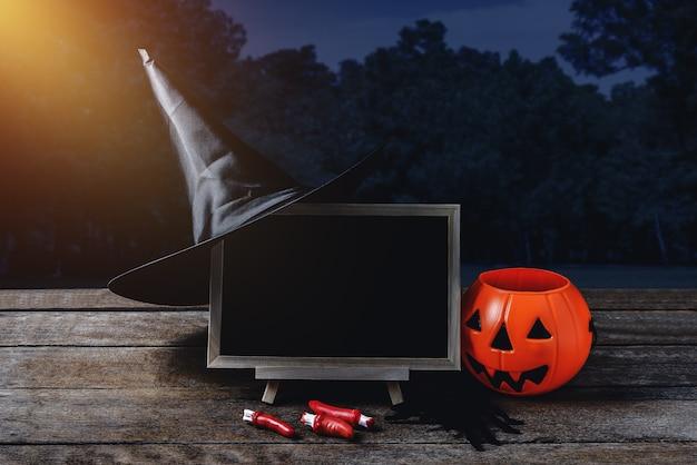 Halloween background. spooky pumpkin, witch hat, spider, chalkboard on wooden floor