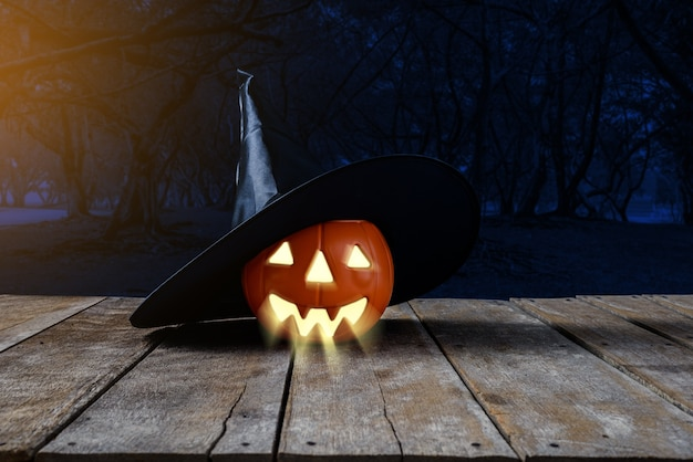 Halloween background. spooky pumpkin, witch hat on wooden floor with moon and dark forest