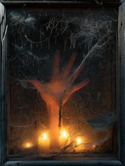 古いウィンドウで怖くて不気味なクモの巣とハロウィーンの背景。ろうそくの光を手に