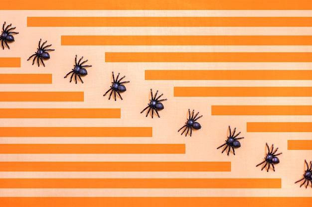 Halloween background with black spiders walking in diagonal row and rectangular stripes in orange.