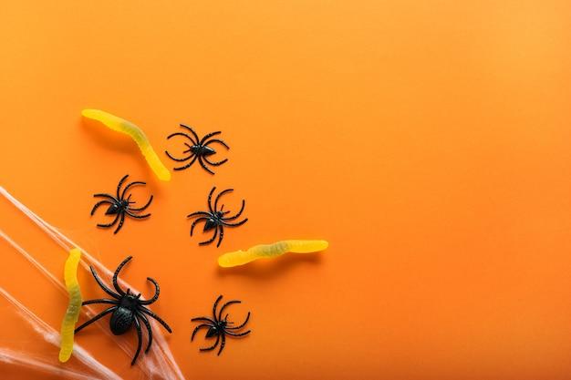 오렌지 배경에 할로윈의 상징으로 사탕 벌레, 거미줄, 거미가 있는 할로윈 배경. 해피 할로윈 개념입니다. 복사 공간이 있는 상위 뷰입니다.