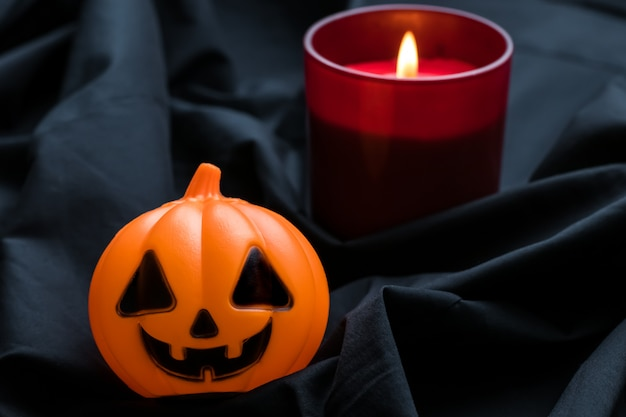 Halloween background with carved pumpkin and glowing candle.