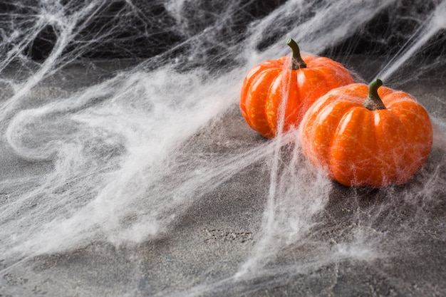 Halloween background with colorful pumpkins and spider web