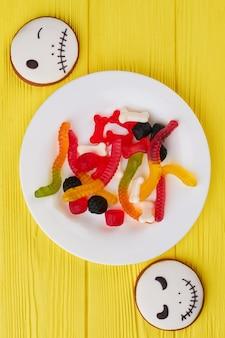 ハロウィーンの背景にクッキーとキャンディーの上面図、カラフルなゼリー菓子とハロー...