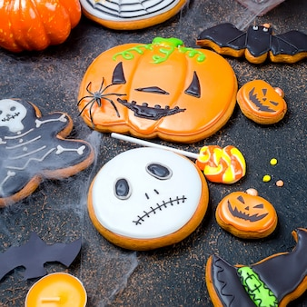 Halloween background with gingerbread, pumpkins and candles