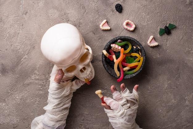 ミイラの手、お菓子、頭蓋骨とハロウィーンの背景