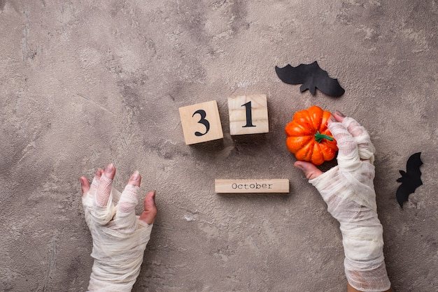 Halloween background with mummyã¢â€â™s hands and wooden calendar